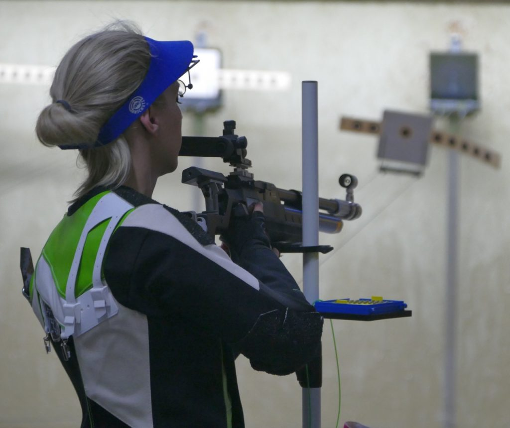 Eine Luftgewehrschützin legt ihr Gewehr auf dem Stativ ab.